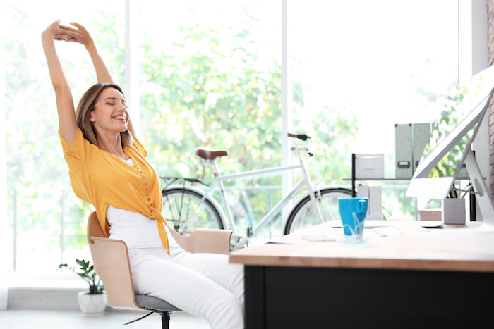 Beautiful young businesswoman stretching in office. Workplace fitness